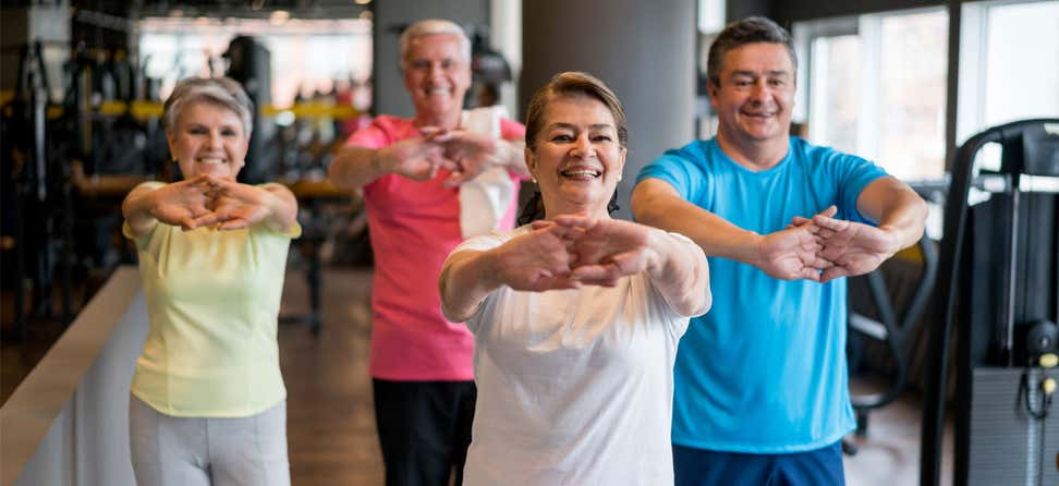 A group of Hispanic older adults are exercising together, doing stretching exercises.