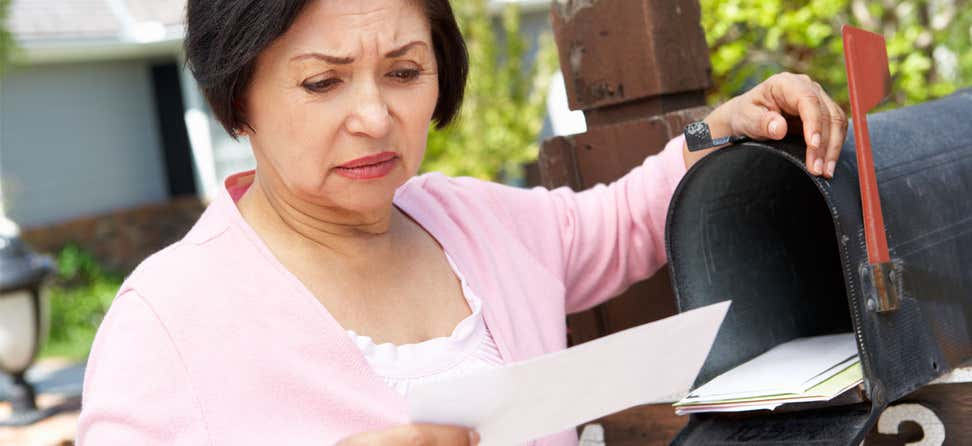 An older Asian woman checks her mail, staring with a confused look at a piece of mail she's picked up.