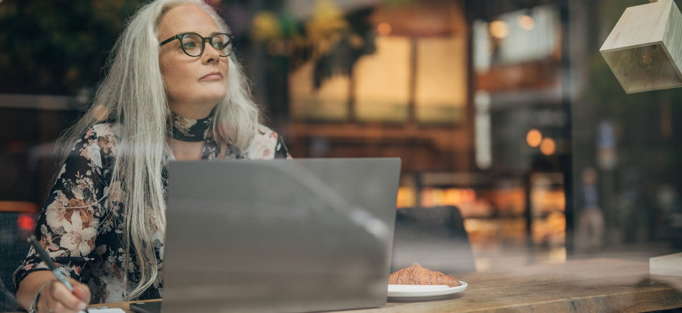 A senior woman wearing glasses sits at her computer in a coffee shop, contemplating a decision and looking out the window.