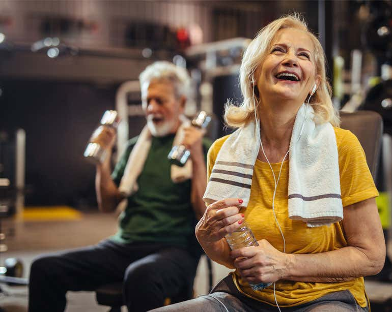 A senior woman in her gym clothes takes a break from exercising while smiling and holding a bottle of water. Her husband is in the foreground seen lifting dumbbells.
