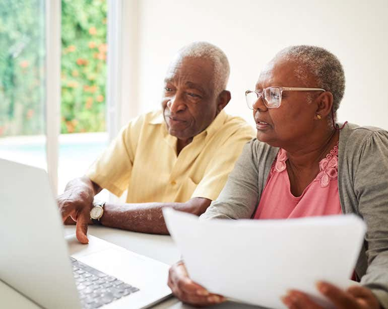 A senior Black couple are working on finances together while using a computer.