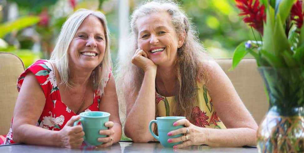 Two senior women sit together at a table enjoying coffee together.