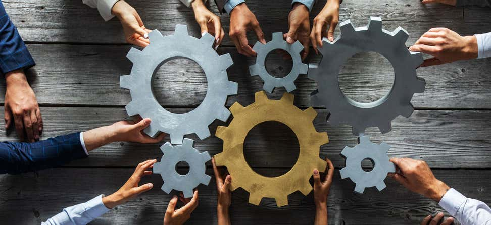 Several hands are holding large cogs in the center of a table, indicating teamwork and having to work together.