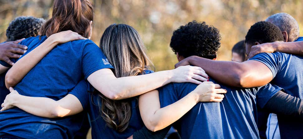 A diverse group of people from the back are in a huddle with their arms around each other's shoulders.