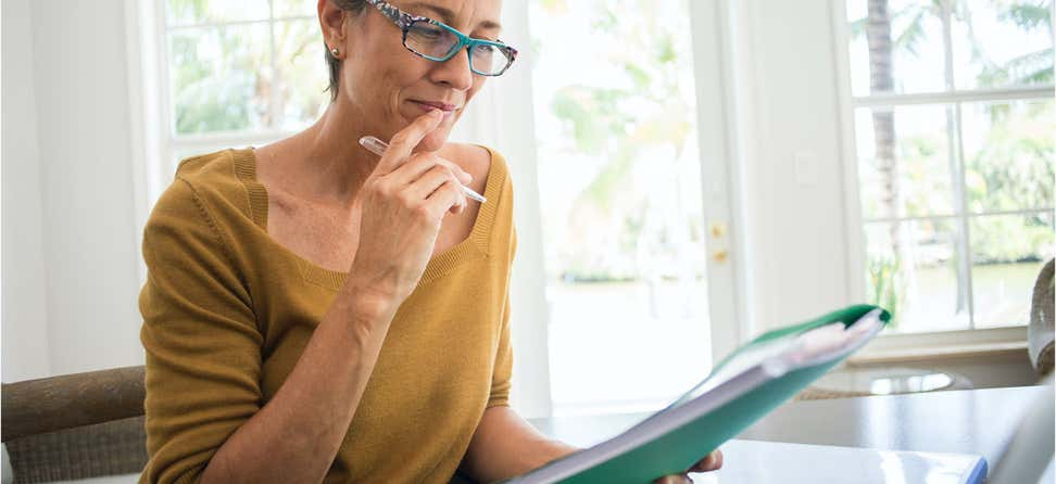 A senior woman is looking over a financial file, contemplating her decisions.