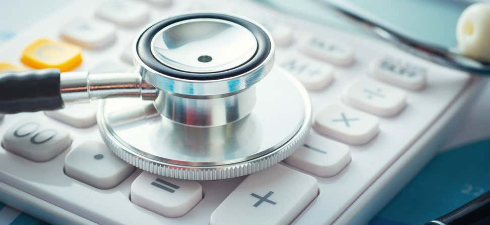 A close up shot of a stethoscope laying on top of a calculator, indicating the cost of health care.