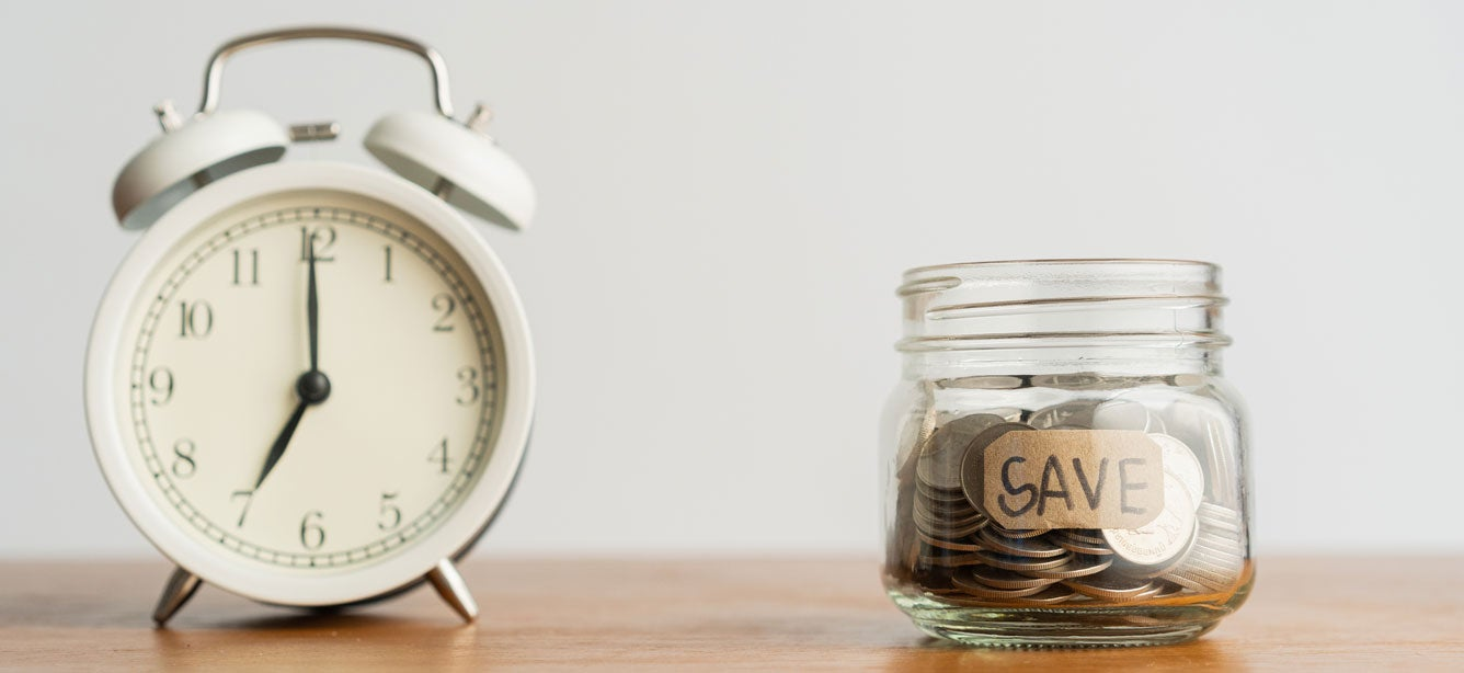 """An old alarm clock sitting to the left of a mason jar labeled """"save"""", indicating a race for time to save money."""