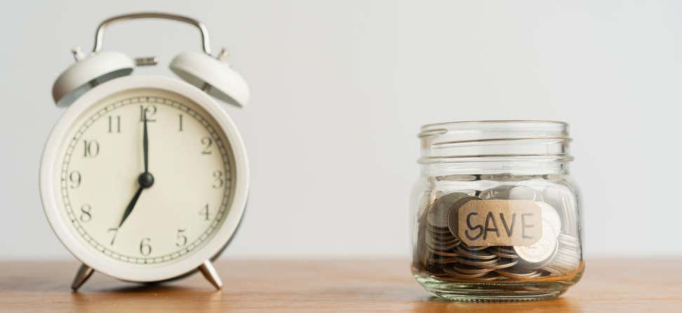 "An old alarm clock sitting to the left of a mason jar labeled ""save"", indicating a race for time to save money."