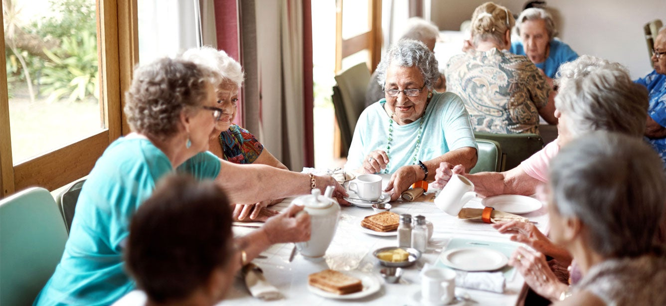 A group of seniors are enjoying their breakfast together in a senior center.