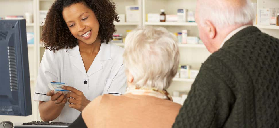A Black female pharmacist is helping an older senior couple, explaining a medication to them as they check out.