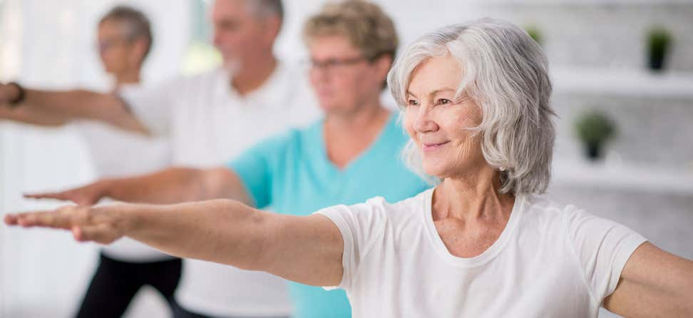 An older woman smiling is doing yoga in a group setting.
