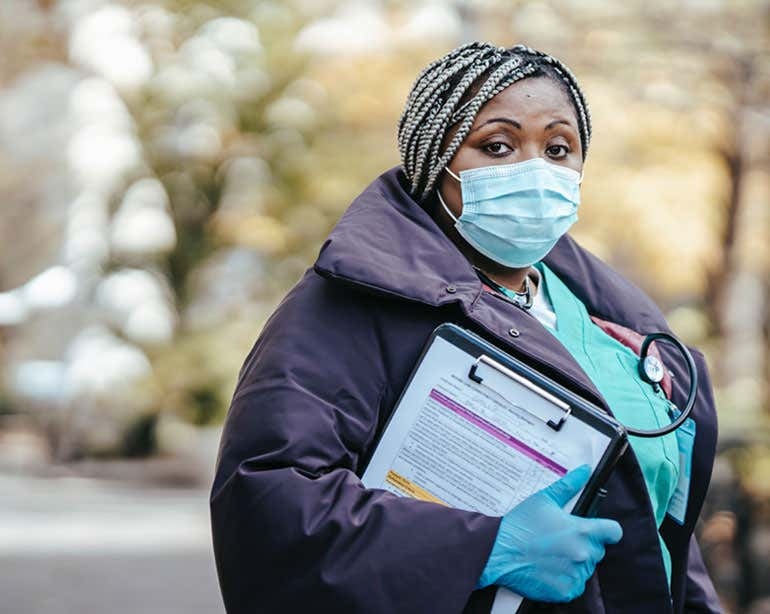 A Black healthcare professional is standing outside with a mask and gloves on, holding a clipboard.