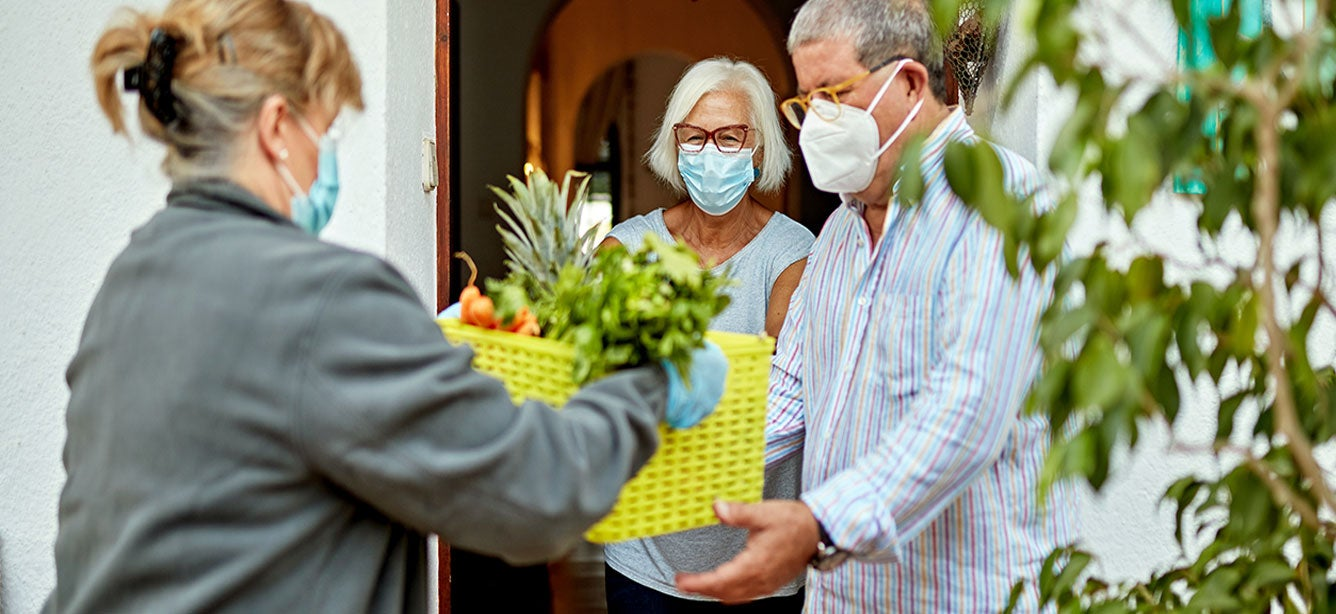 senior masked caucasian couple receives a grocery delivery at home during the COVID-19 quarantine