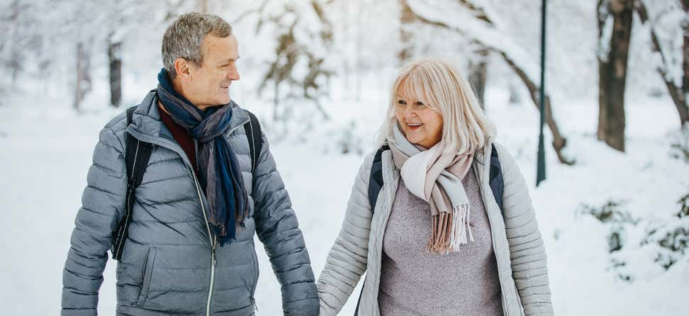 A senior couple is walking hand-in-hand outside in the winter, where the foreground is covered in snow.