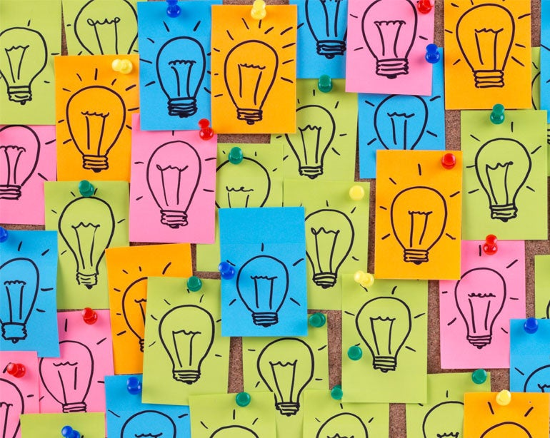 lightbulbs drawn on blue, yellow, and orange sticky notes pinned to bulletin board