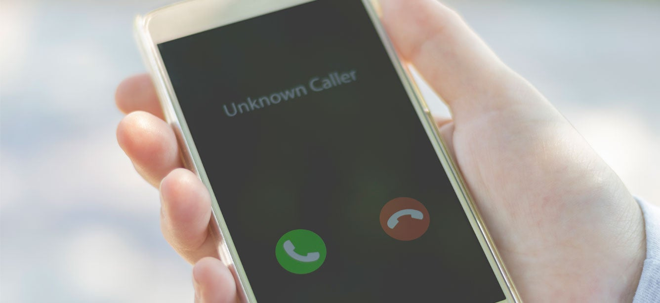 """A man holds a cell phone in his hand that says """"Unknown Caller"""", likely indicating a scam."""