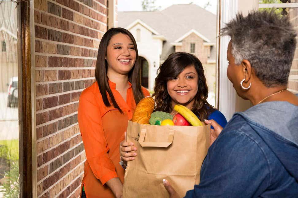 Two teenage girls delivering food bag to older black woman