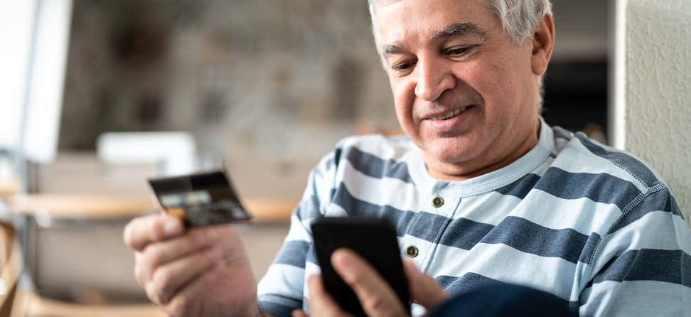 A senior Hispanic man is using his credit card while making an online purchase.