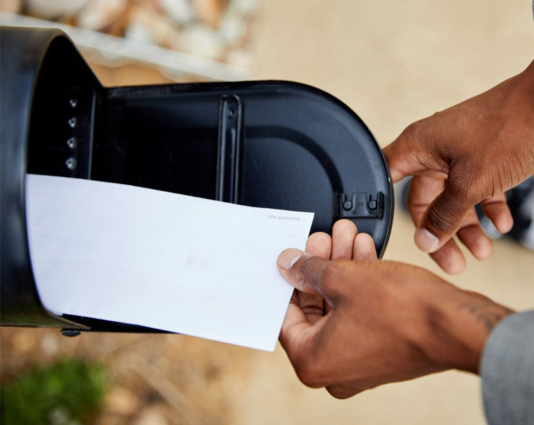 A Black senior man is placing an envelope in a mailbox.
