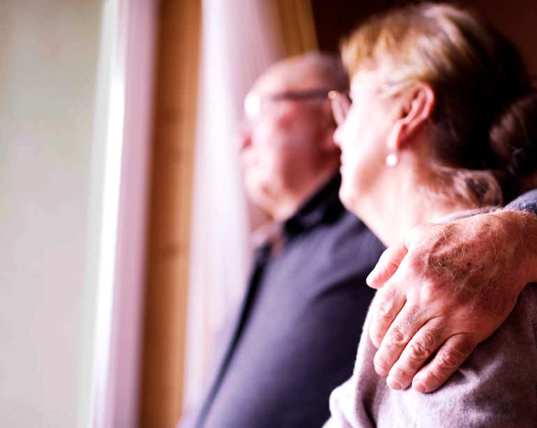 A senior couple embraces each other, staring out of their window.