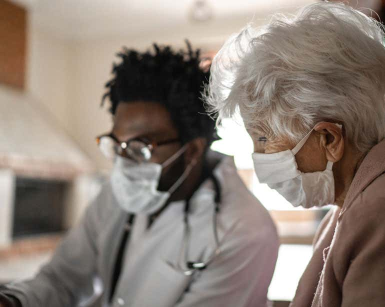 An older woman wearing a mask is having an in-person health care visit with a doctor during the pandemic.