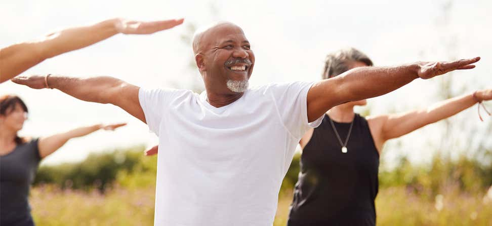 A Black senior man is practicing yoga in the park with other older adults.