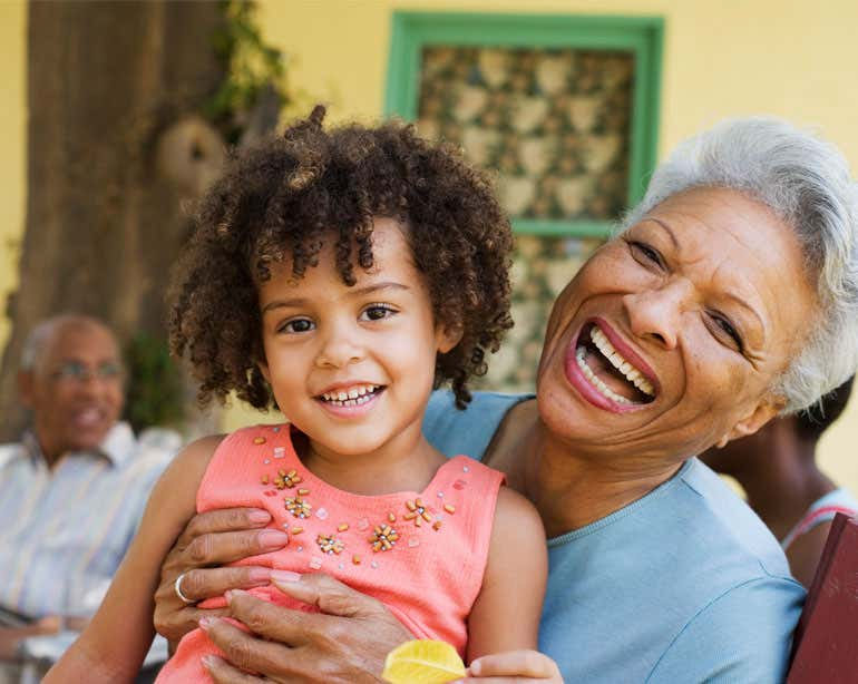 A senior Black woman is holding her granddaughter in her lap during a family get together outside.