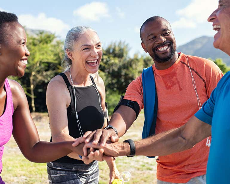A group of diverse older adults put their hands in for a team high five while exercising outside.