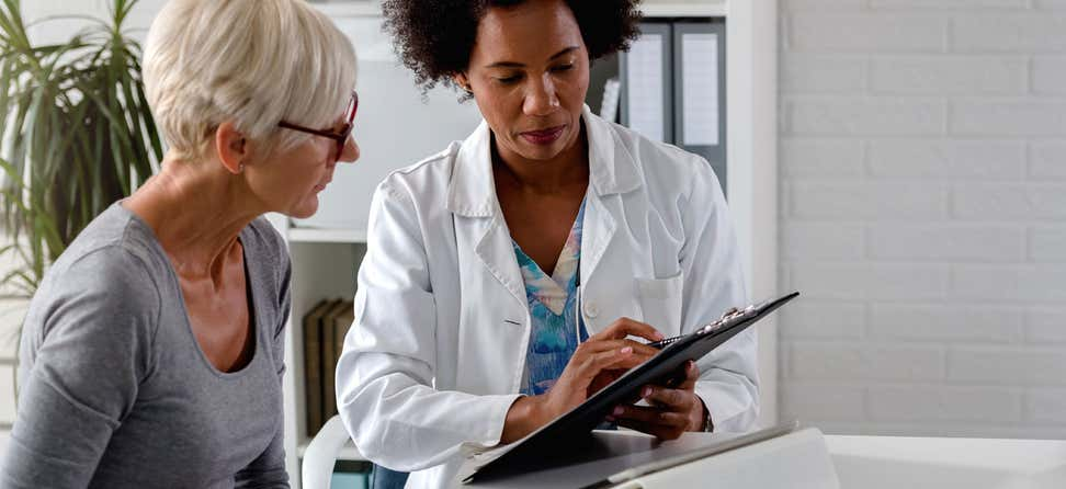 senior white woman confers with black female doctor with clipboard