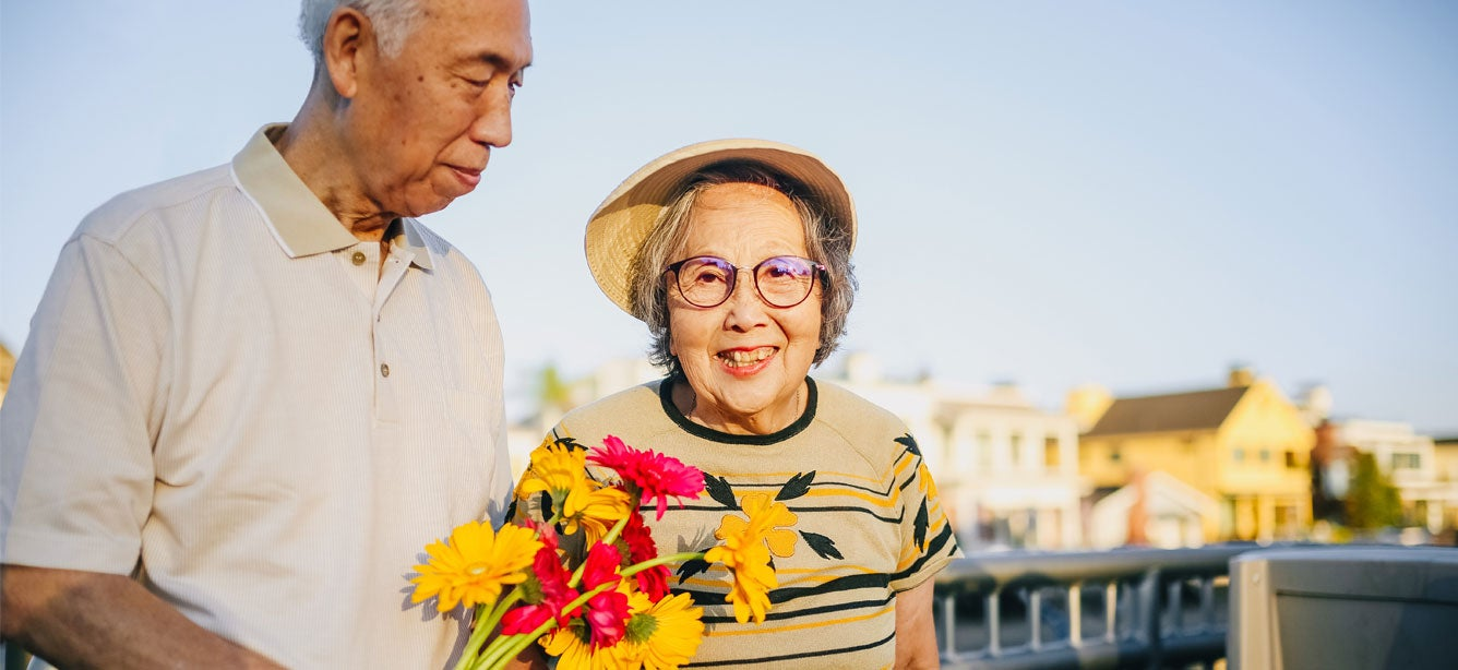 A senior Asian couple walks hand-in-hand outside, where the husband is carrying a bouquet of flowers as the wife smiles at the camera.