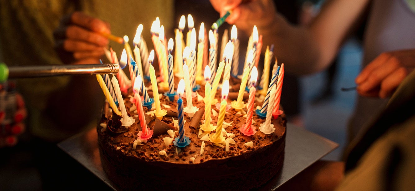 A close up shot of a birthday cake with a lot of candles being lit.