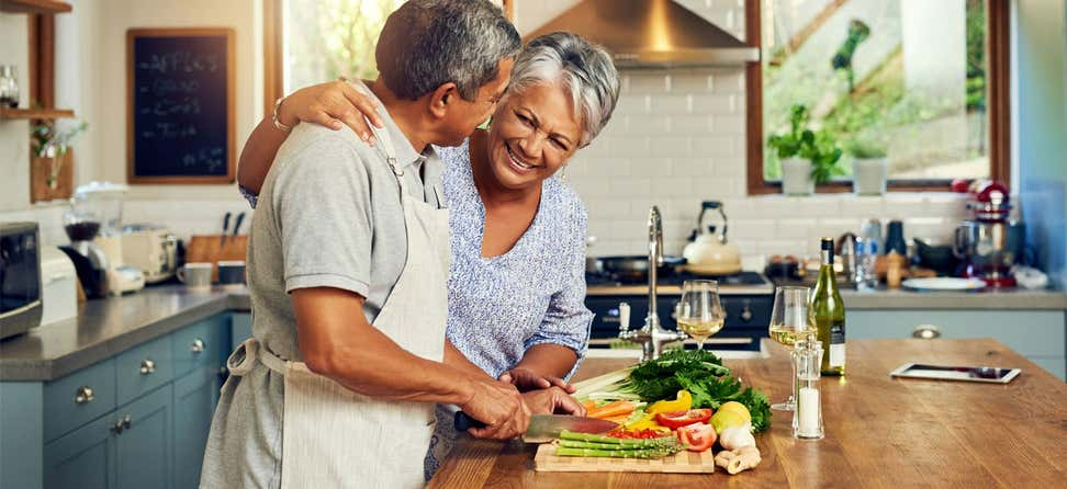 A Black senior couple is preparing a meal together in their home kitchen.