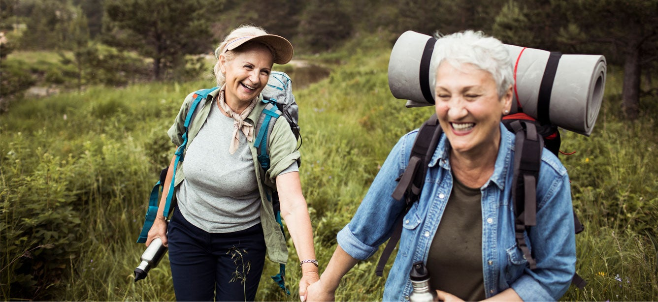 A lesbian senior female couple are outdoors hiking and holding hands.