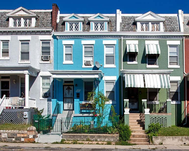 Street view of three colorful row homes in a city neighborhood.