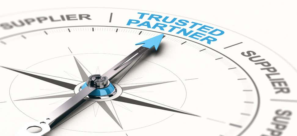 "An up-close shot of a compass, where the needle points toward the words ""Trusted Partner""."