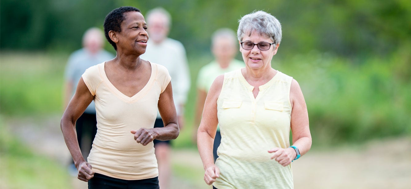 Two senior women are walking outside in the park, getting exercise together.