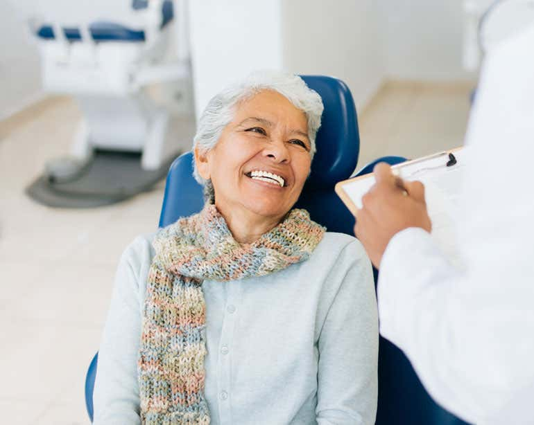 A Hispanic older woman is sitting in a dental office chair, talking to her dentist.