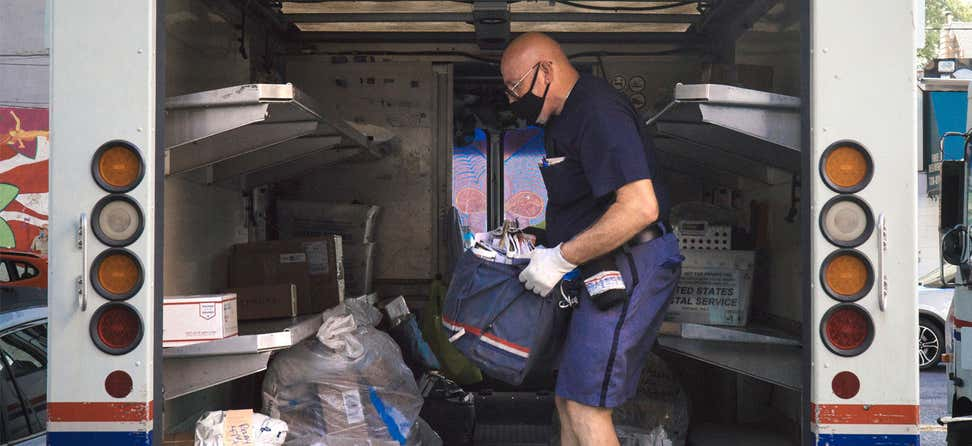 A masked postal worker in New York City holds a canvas bag full of mail and is loading it into his vehicle before heading out for the day.