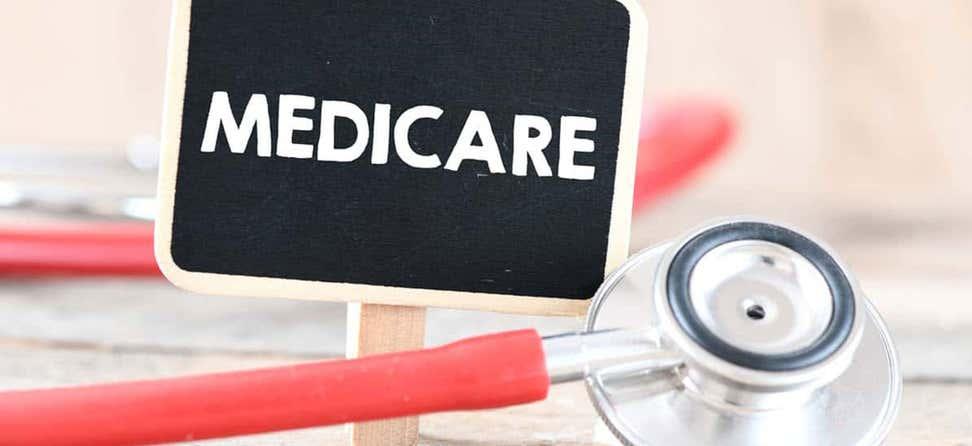 """Un primer plano de un estetoscopio junto a un pequeño letrero de pizarra que dice """"Medicare"""" en mayúsculas."""