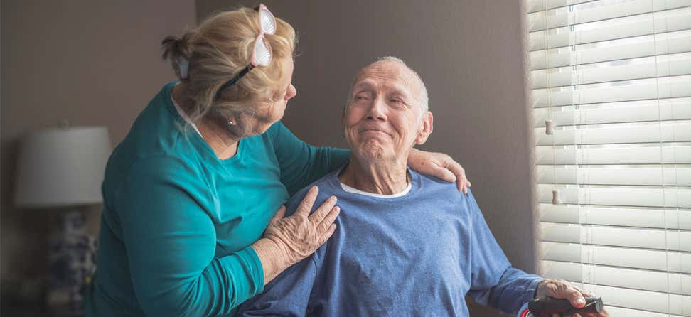 An older female caregiver looks fondly on a much older senior man who's sitting down, smiling by a window.