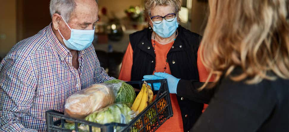 A professional from a community-based organization is delivering a plastic cart full of fresh produce to an elderly couple during the pandemic.