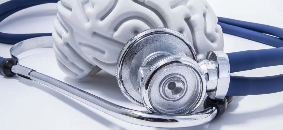 An up close shot of a model plastic brain surrounded by a stethoscope.