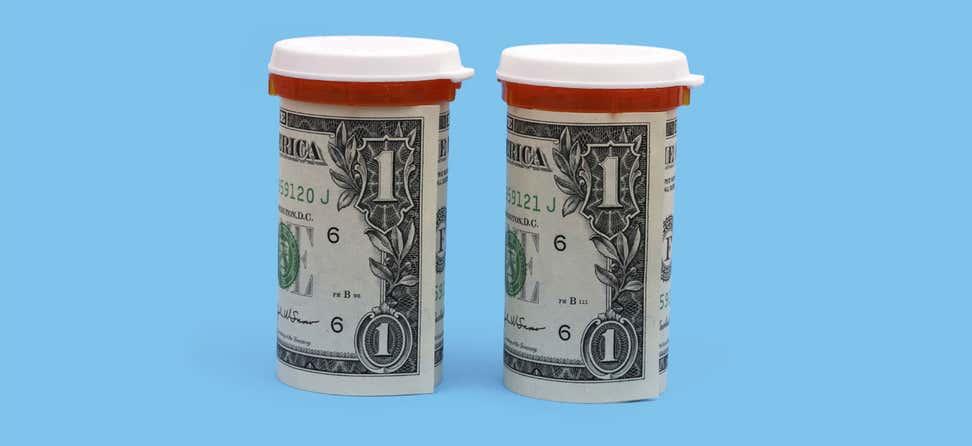 Two dollar bills are rolled up around prescription bottles.