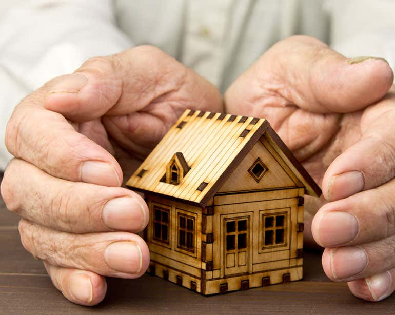 Senior hands are seen cupping a small wooden house, indicating that they're protecting their investment.