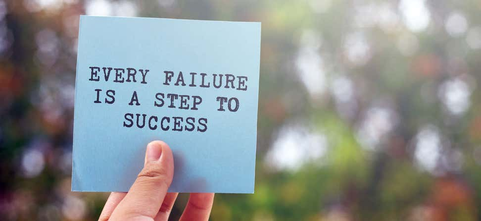 "A close-up shot of an inspirational quote, ""Every Failure Is A Step to Success"" on a blue note card."