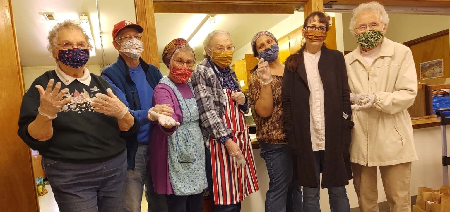 Seven older adults wearing masks in community center.