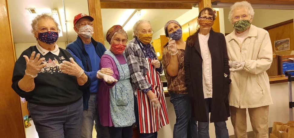 Seven older adults wearing masks in community center.