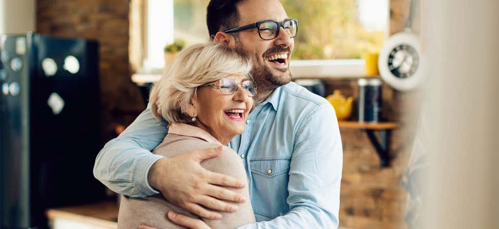 A senior Caucasian woman is seen embracing her younger male caregiver, both are smiling.