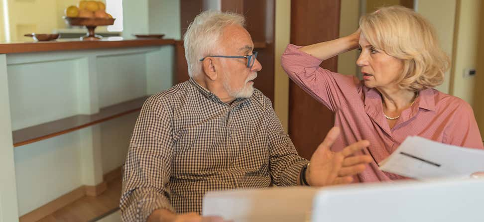 An older adult Caucasian couple is discussing their financial options while sitting at their kitchen table.