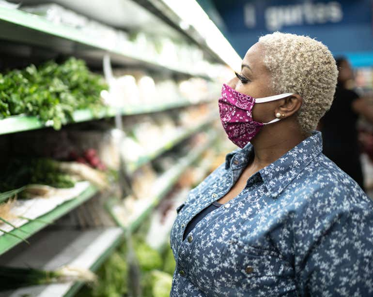 Older Black woman in produce section of grocery store, wearing face mask.